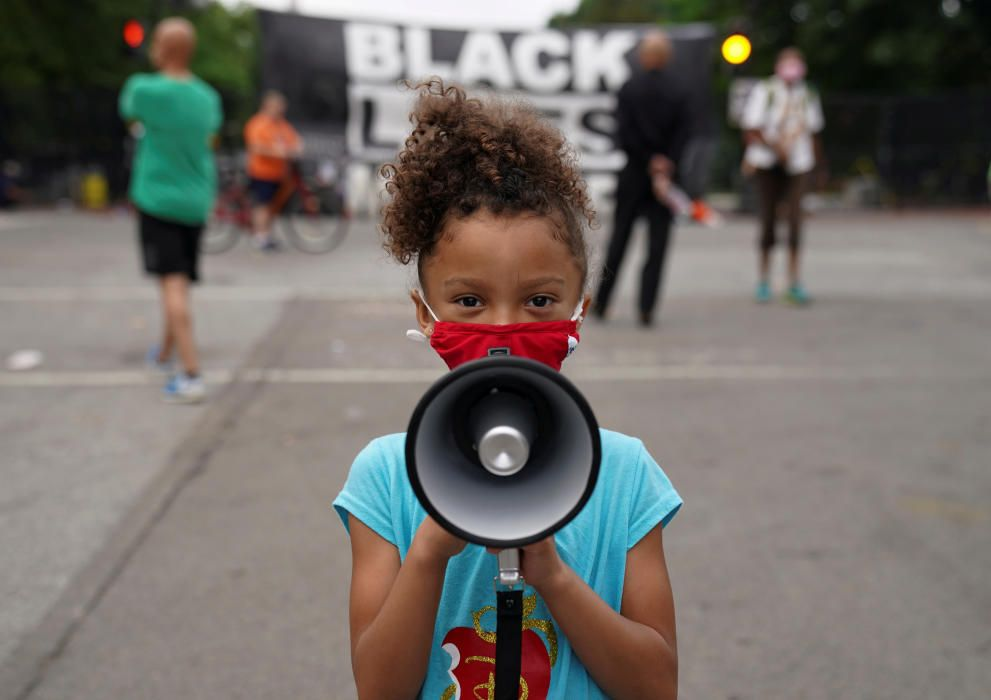 A girl holds a bullhorn in front of a Black ...