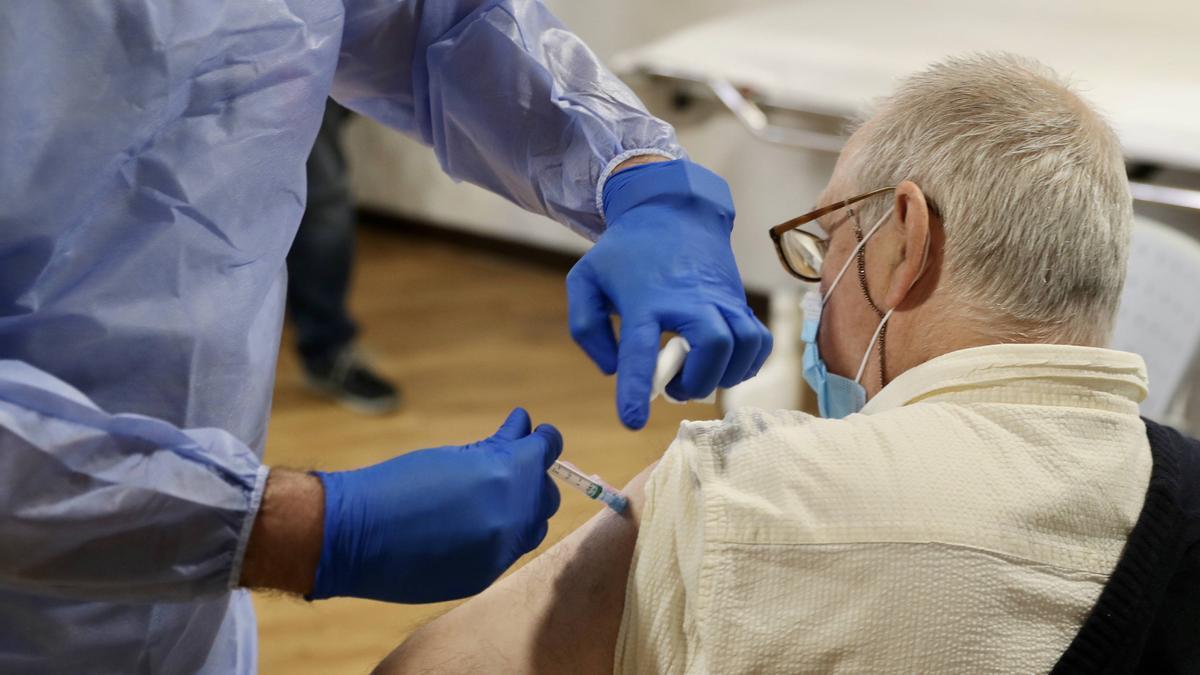 Un sanitario administrando una vacuna contra la covid.
