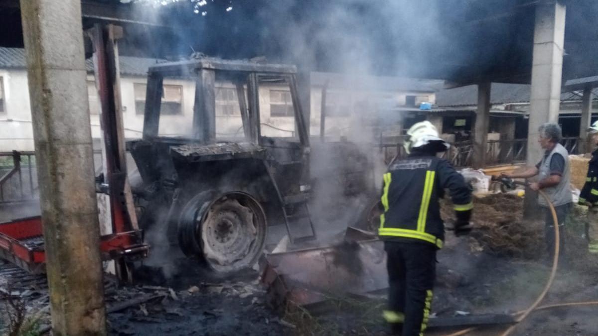 Labores de extinción en el tractor que ardió esta mañana en Merza.