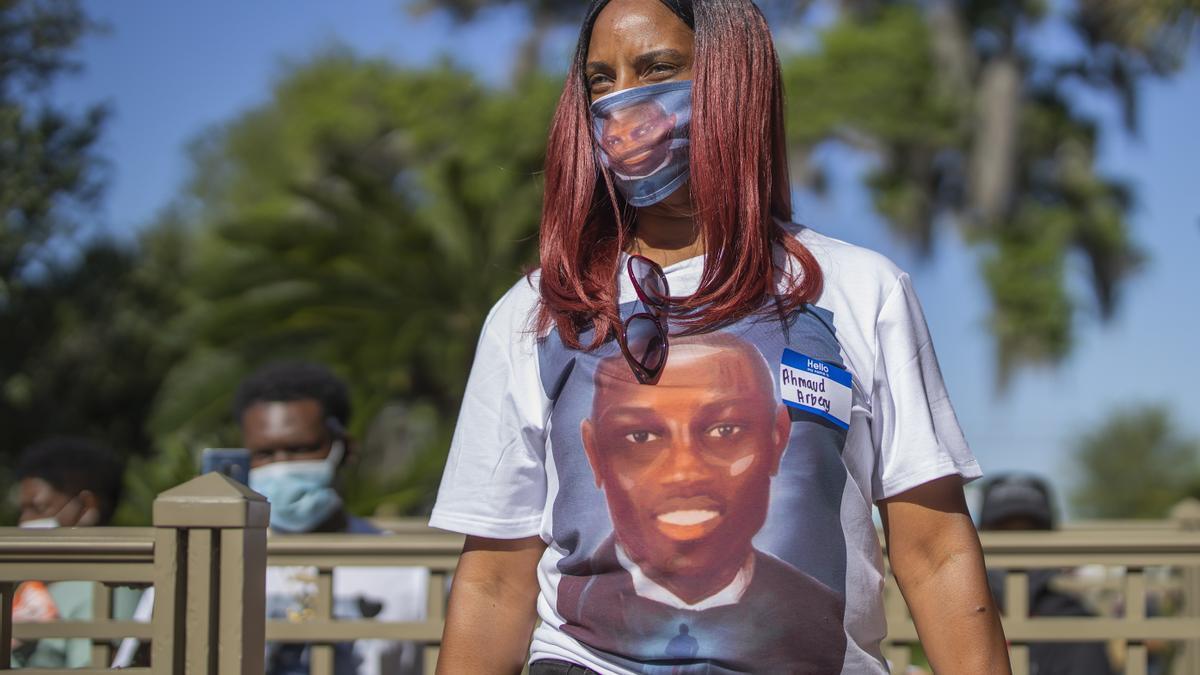 Una mujer utiliza una mascarilla y una camiseta con el rostro de Ahmaud Arbery.