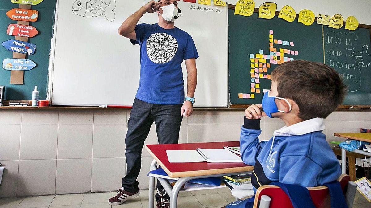 Un profesor y un alumno, durante una clase de Infantil en un colegio.