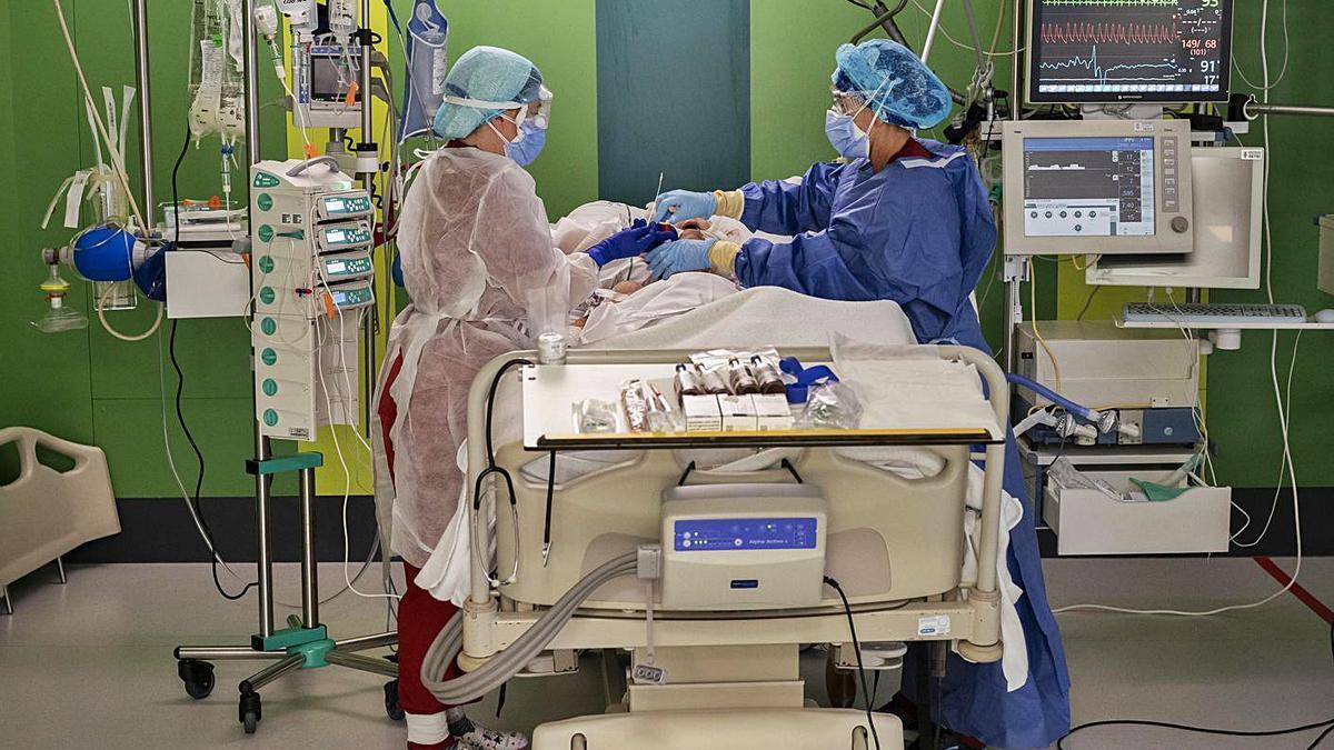 Dos enfermeras atienden a un paciente en la UCI. | Germán Caballero