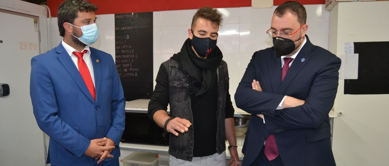 El alcalde de Valdés, Óscar Pérez; Jonathan González; y Adrián Barbón, en la pastelería de Busto.
