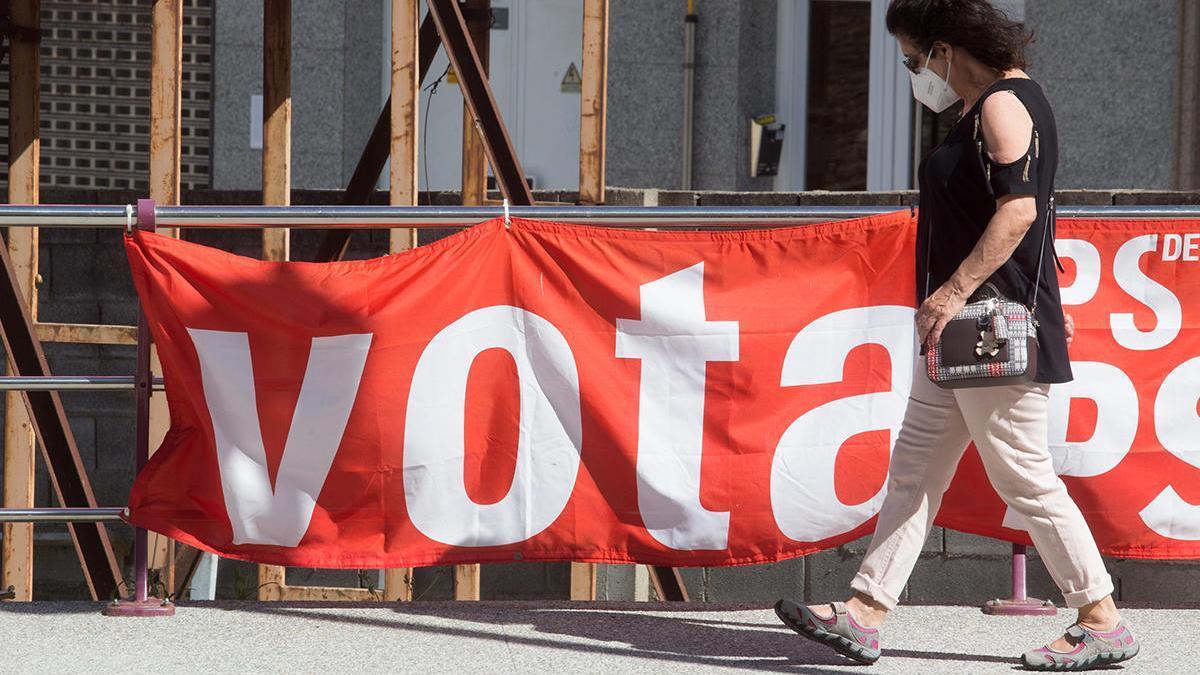 Una mujer protegida con mascarilla pasea junto a un cartel electoral del PSdeG en Foz // Carlos Castro / (Europa Press)