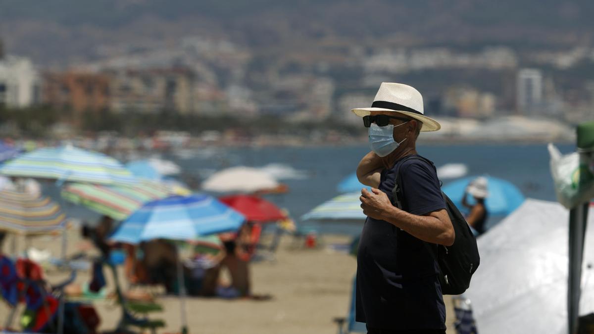 Un hombre con mascarilla en una playa de Málaga