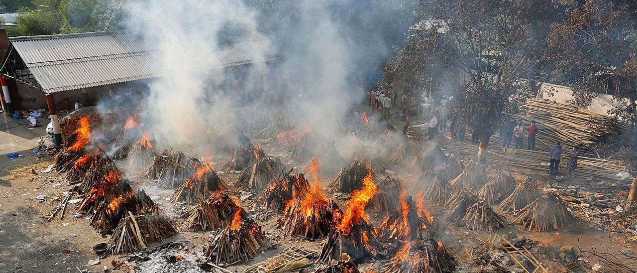 Piras ardiendo en un campo de cremación masiva en Nueva Delhi de víctimas  del covid.    EFE