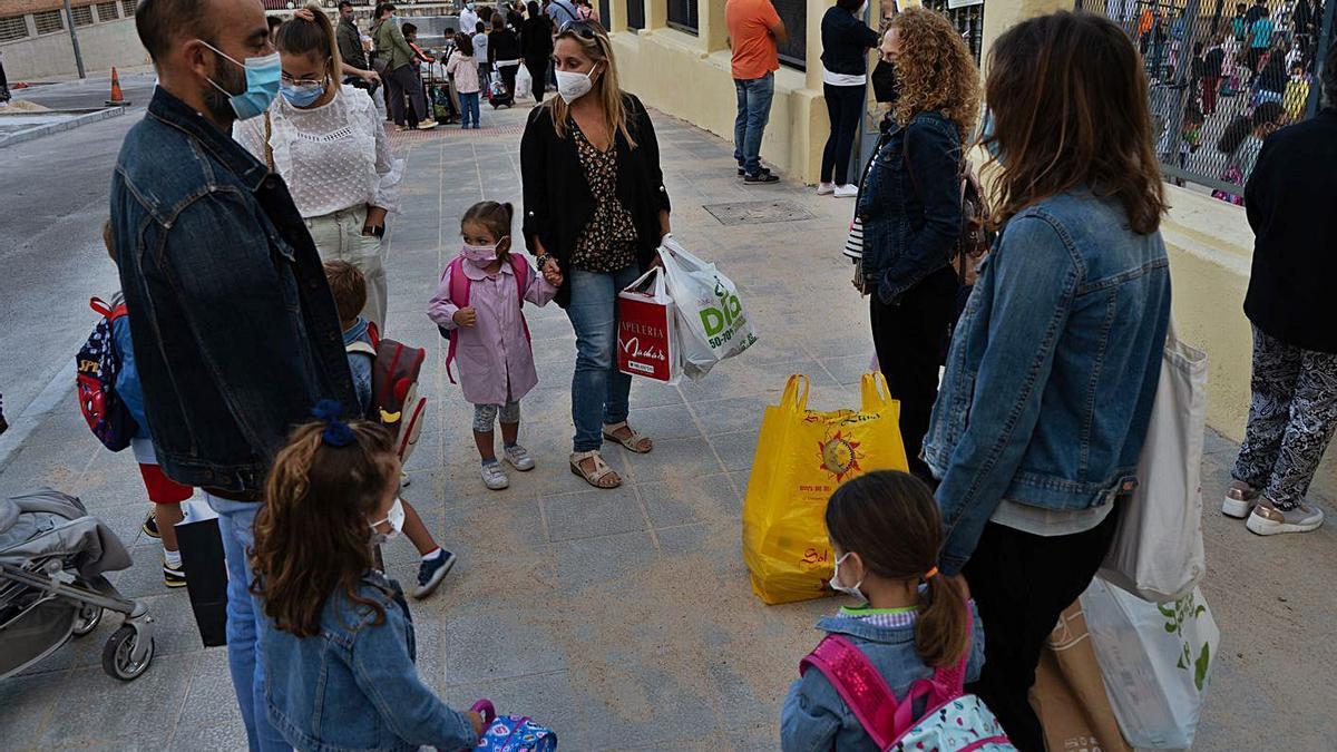Padres y escolares en elcolegio de San José de Calasanz; y dos niñas entran al centro.