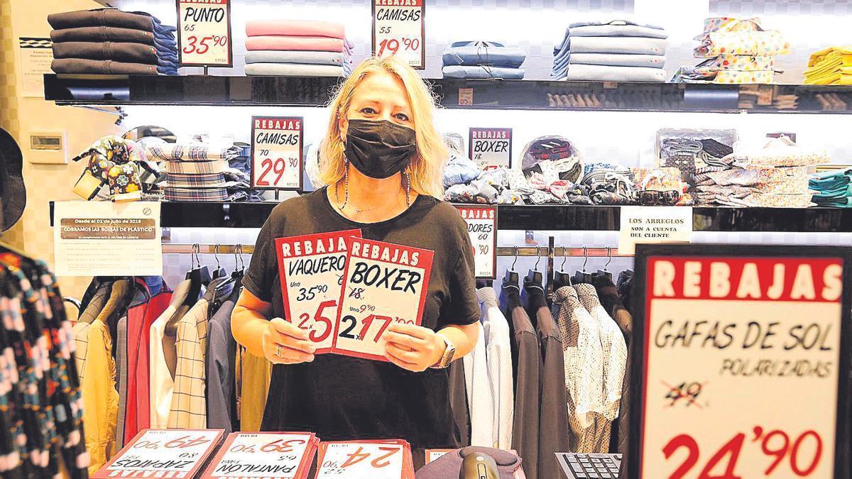 Blanca Martínez, de la tienda Shenior Collection, posa con los carteles de las rebajas