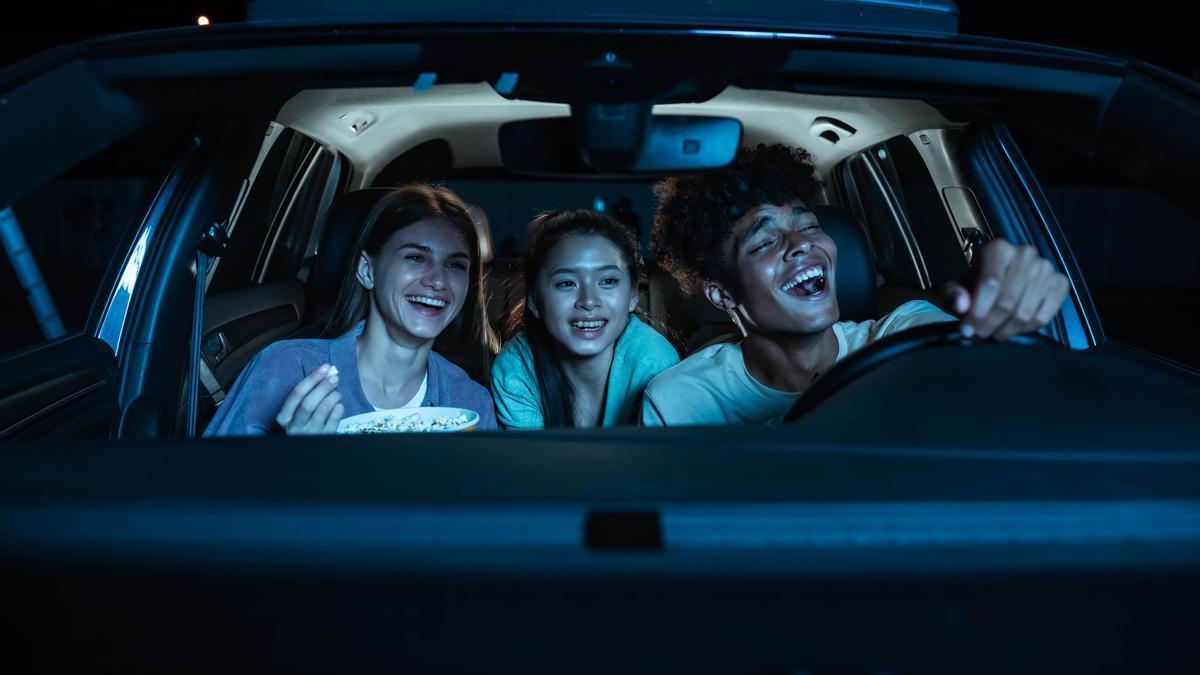 Tres amigos viendo una película desde el coche.