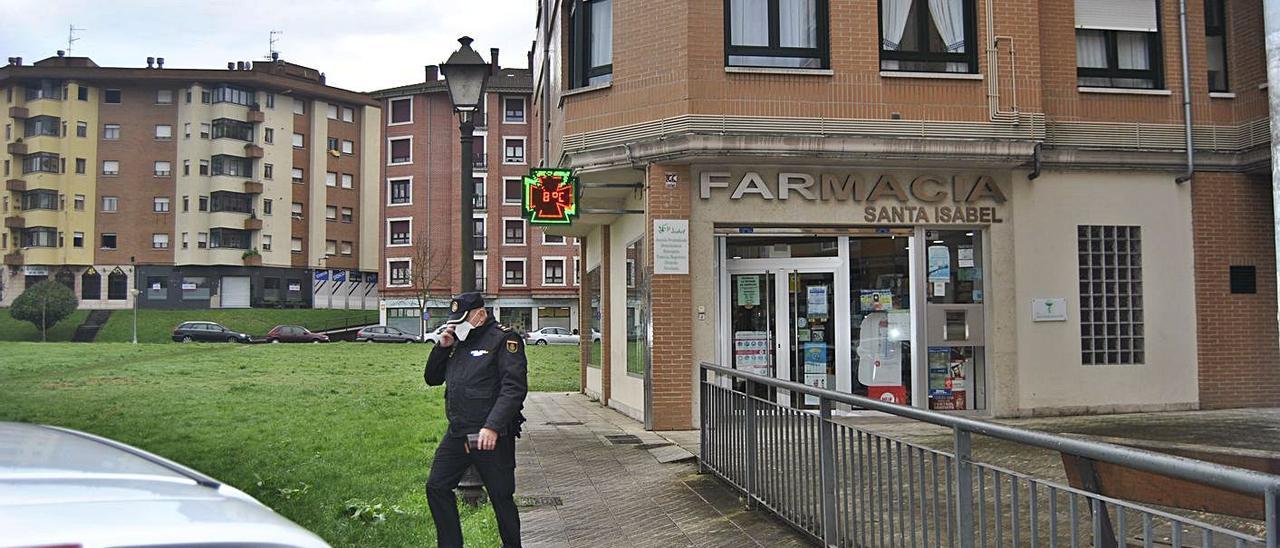 Un agente de la Policía Nacional, ayer, saliendo de la farmacia atracada en Lugones. | A. I.