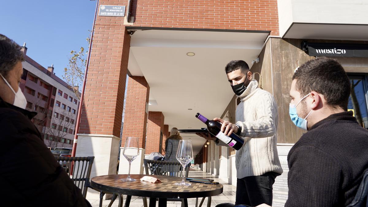 Un camarero sirve un vino a dos clientes en una terraza.