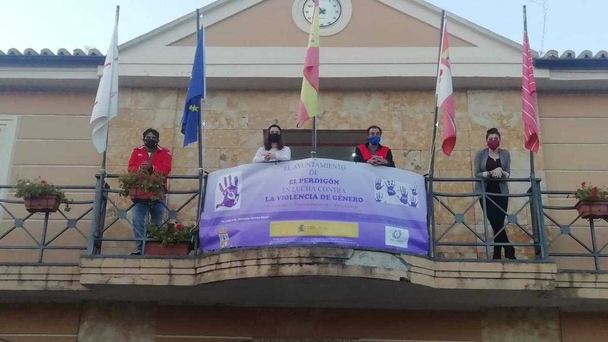 El alcalde y concejales del Ayuntamiento de El Perdigón, en el balcón municipal en el que luce la pancarta diseñada por el 25-N.