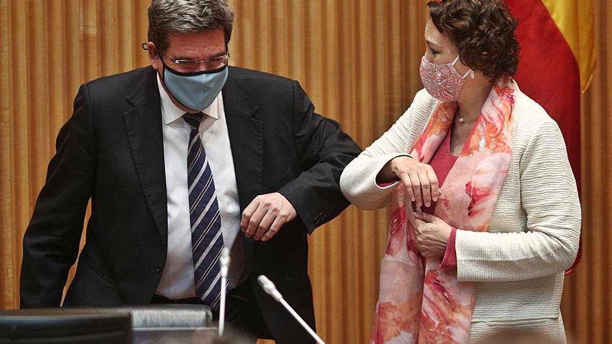 El ministro Escrivá saluda a la presidenta de la Comisión, Magdalena Valerio.     // E. P.