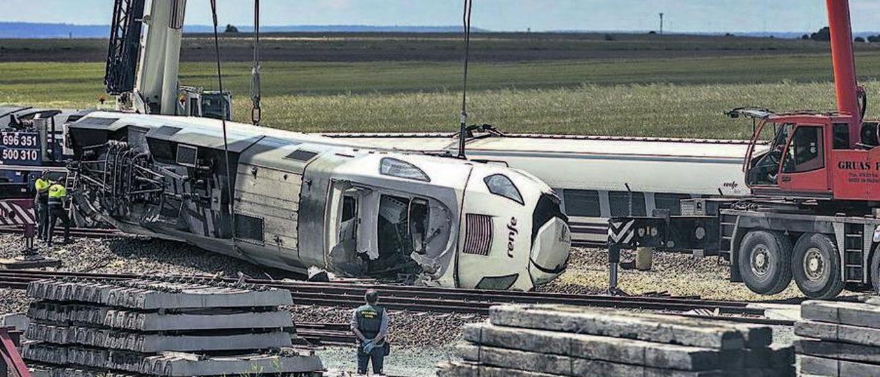 Tres grúas son necesarias para retirar de la vía y las inmediaciones el tren accidentado.
