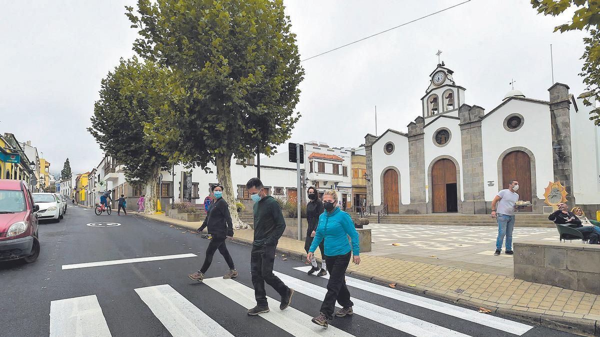 Varias personas cruzan un paso de peatones frente a la iglesia de Valleseco, en Gran Canaria