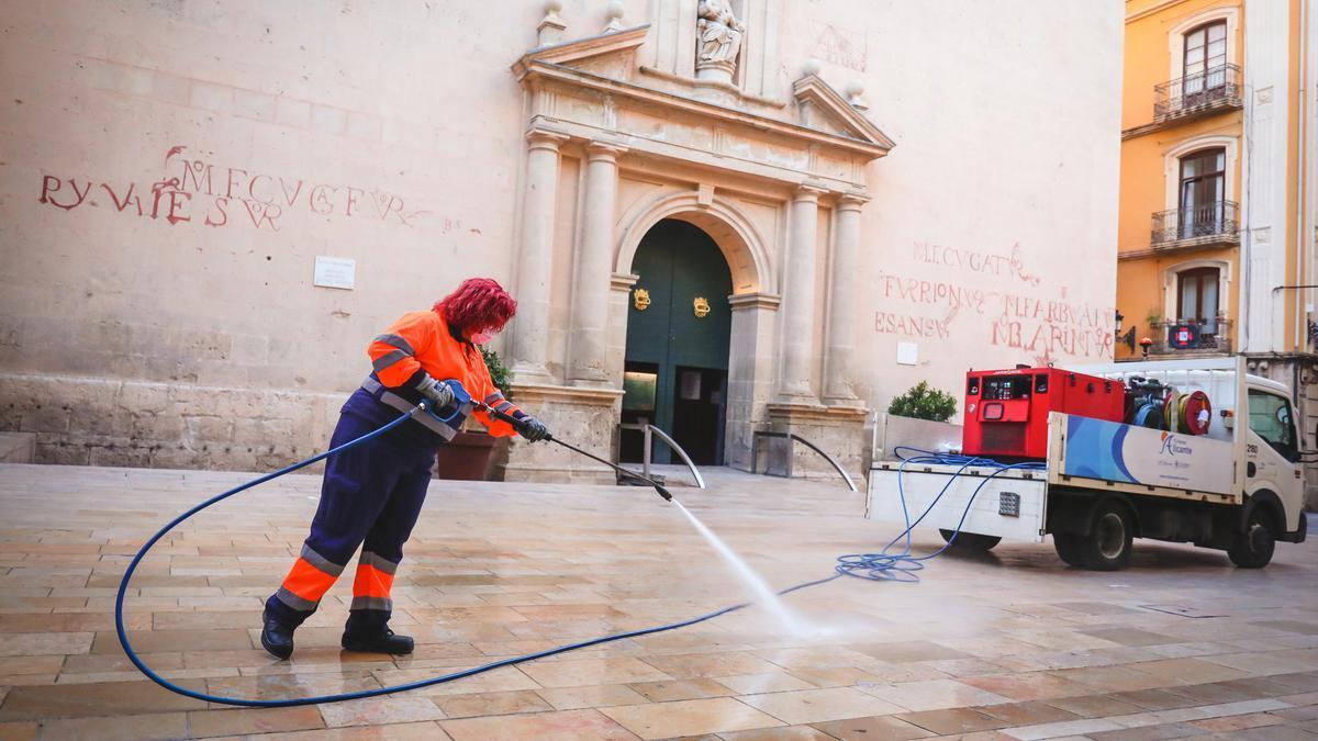 Una trabajadora limpia a presión la plaza de la Concatedral de San Nicolás