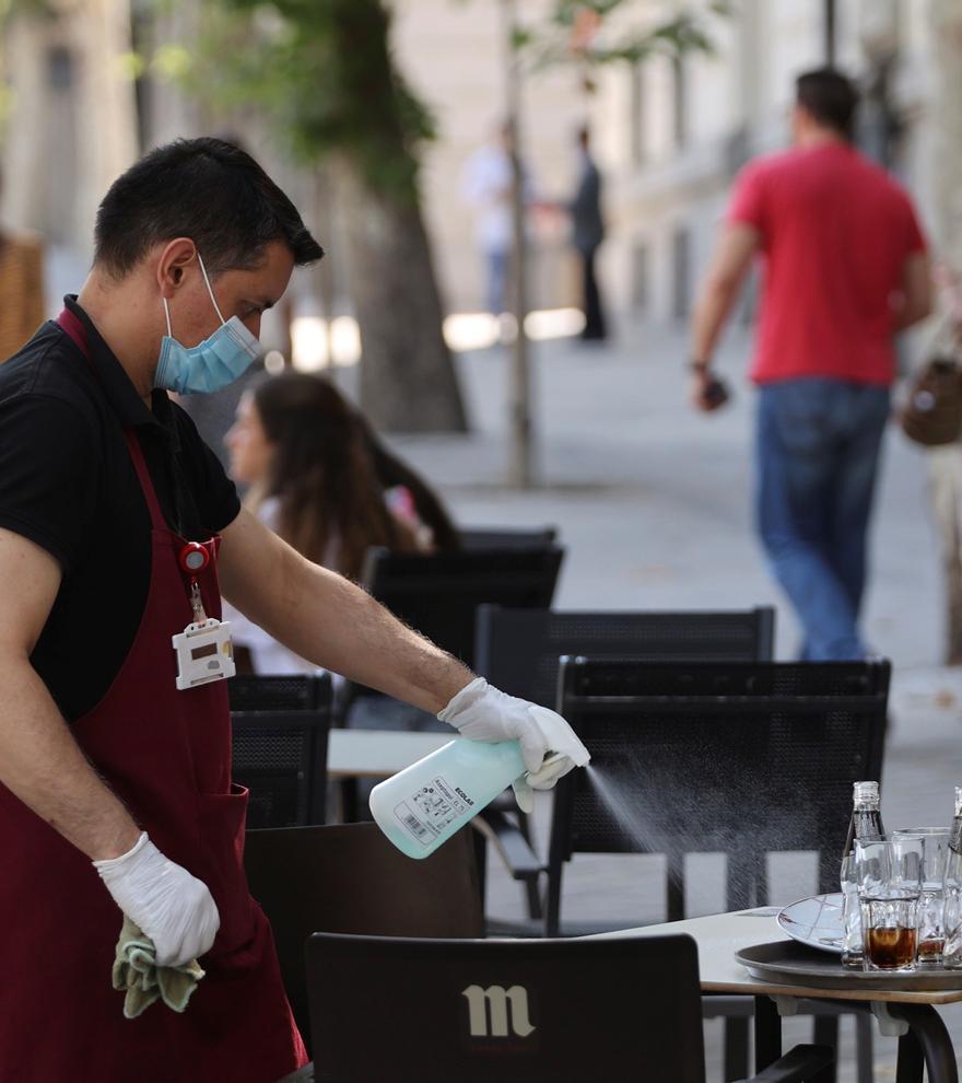 Un trabajador de la hostelería desinfecta una de las mesas ante la pandemia de coronavirus.
