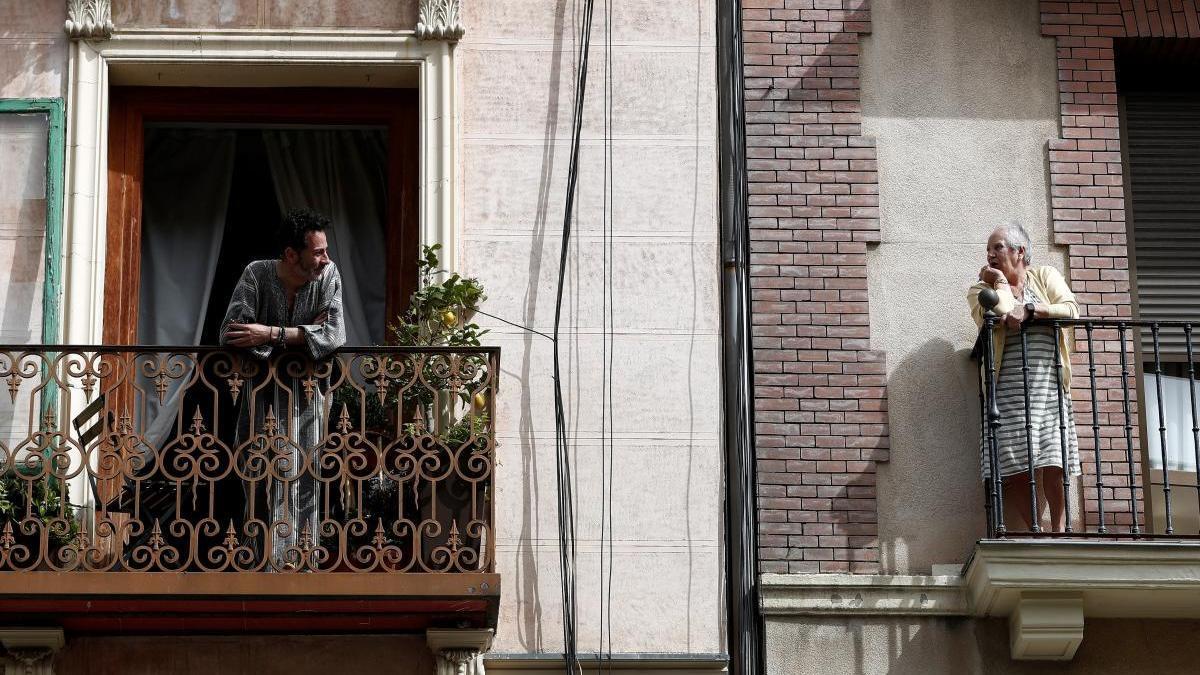 Dos vecinos conversan en el balcón de sus casas en Madrid.