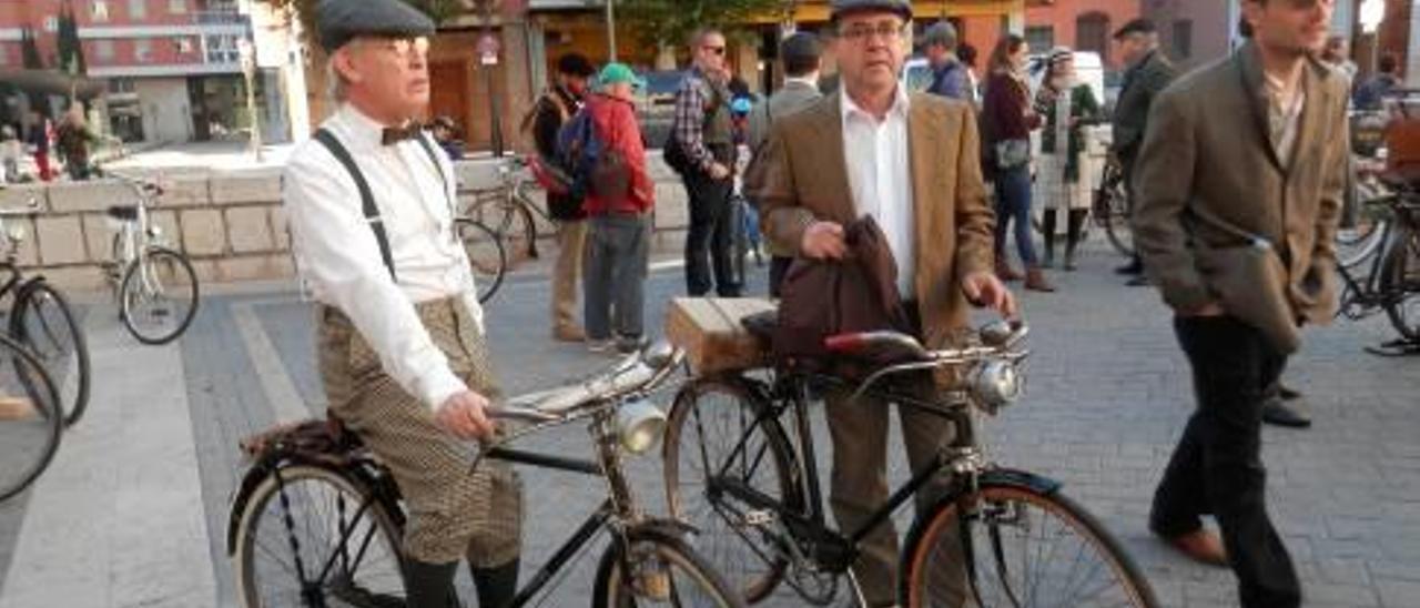 Decenas de aficionados pedalearon hacia atrás en el tiempo por las calles de Alzira en el segundo encuentro de bicicletas clásicas celebrado el pasado domingo.Momento en que algunos de los participantes pasan por delante de la iglesia de Santa Catalina durante un recorrido por el centro de la ciudad. Una bicicleta convertida en un auténtico taller de pintura con las obras de arte incluidas en el portamaletas. Dos de los paticipantes debidamente ataviados con trajes de época esperan en la Plaça del Carbó la salida de la comitiva. El participante de Yecla que finalmente se llevó el trofeo por su bici con la cabra incorporada junto a uno de los miembros de la organización de la «Twwed Red» «Vell i Sense Rovell» de Alzira. f pascual fandos