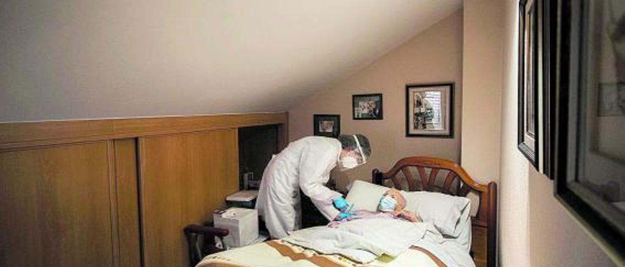 Una sanitaria vacuna a una anciana en su domicilio. | GERMÁN CABALLERO