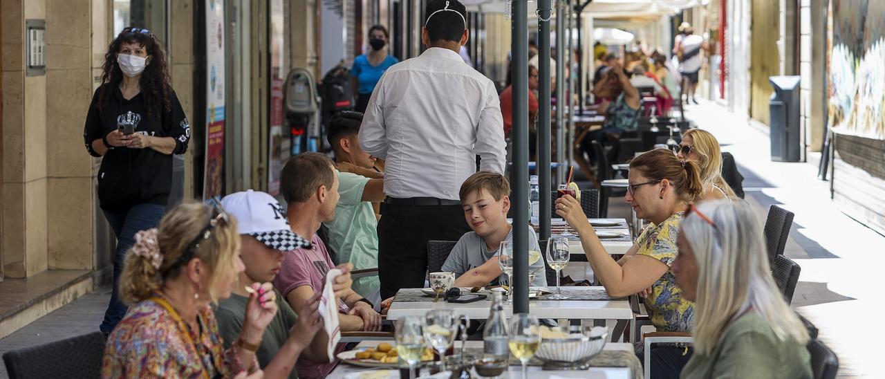 Un camarero atiende a los clientes en una terraza de Alicante.