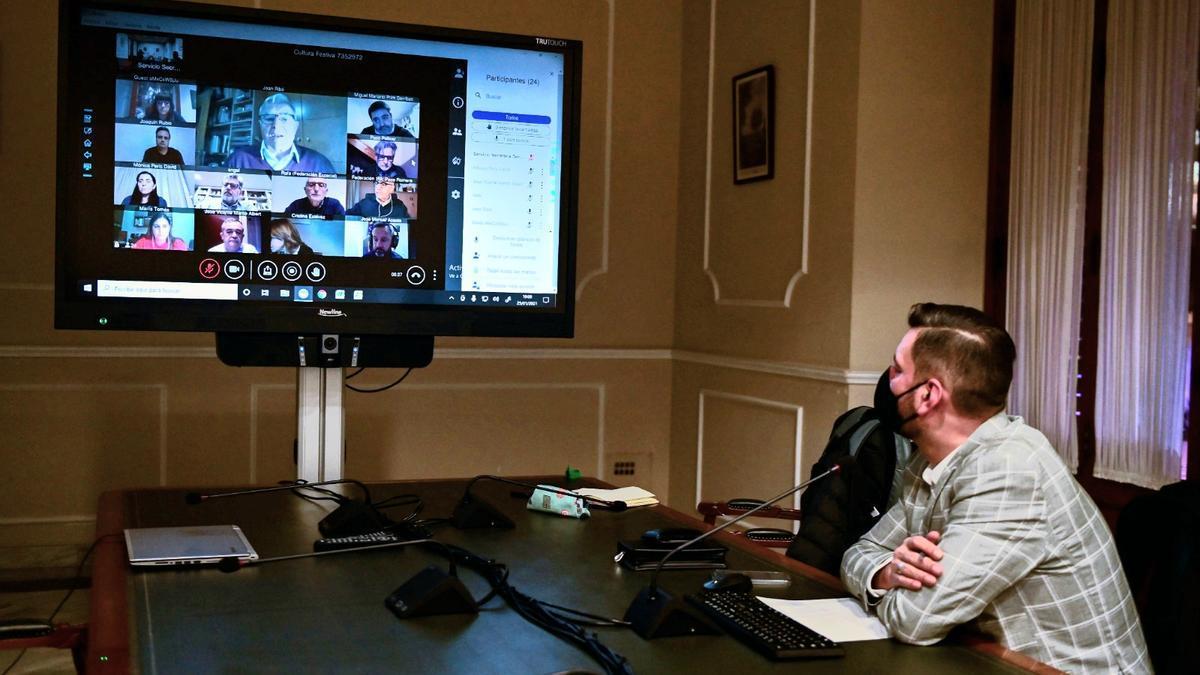 Carlos Galiana sigue la videoconferencia desde su despacho. En el centro de la pantalla, Ribó.