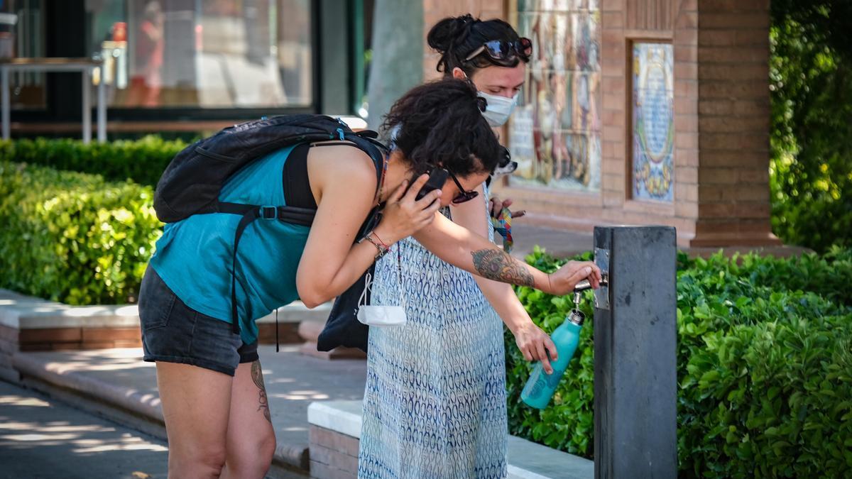 Dos mujeres llenan una botella en una fuente de Badajoz, ayer viernes.