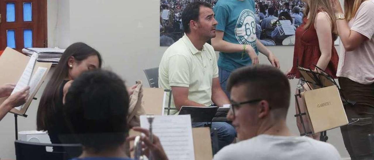 Un momento del ensayo de la Banda de Música de Avilés en su local, con Iván Cuervo con polo amarillo.