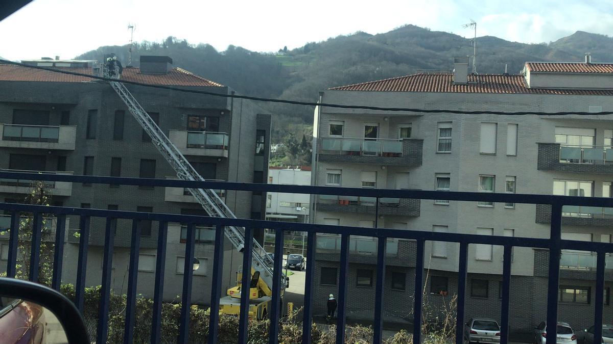 Los bomberos actúan sobre el tejado de las viviendas de Sotiello. / L. Camporro