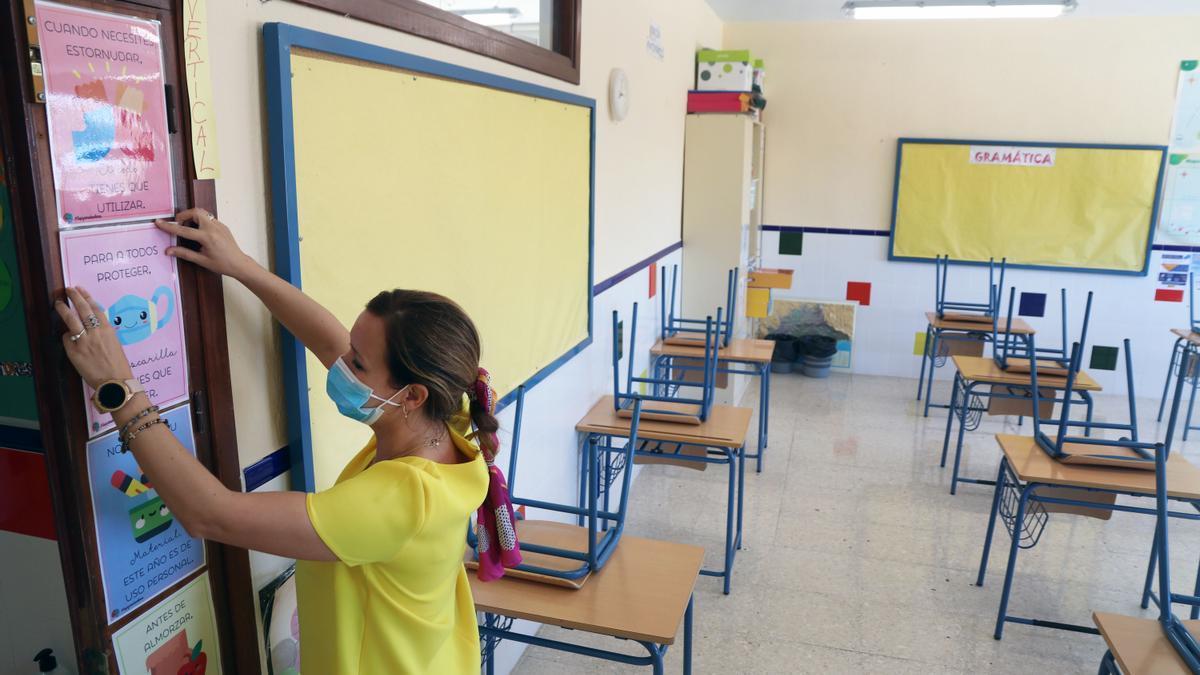 Una profesora coloca carteles de medidas preventivas ante el COVID-19 en el aula antes del inicio del curso.