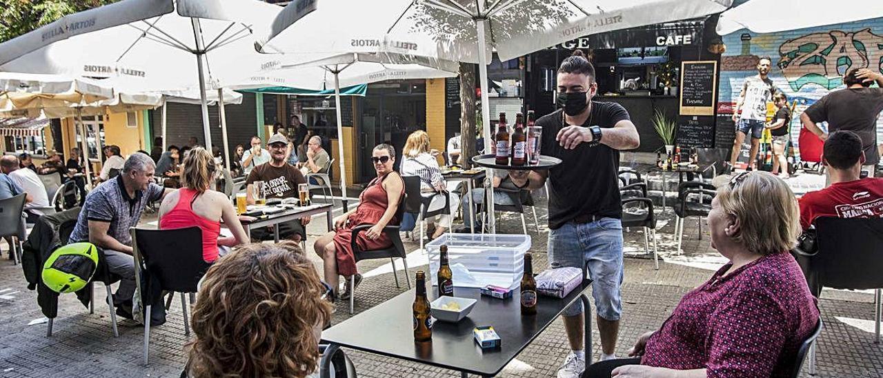Un camarero debidamente protegido atiende una mesa en una terraza de Alicante. PILAR CORTÉS