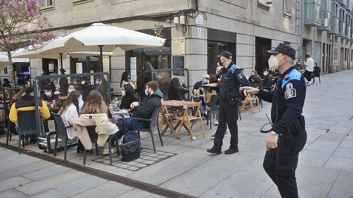Agentes de la Policía Local controlan las medidas de seguridad en las terrazas de Pontevedra.     // R. VÁZQUEZ