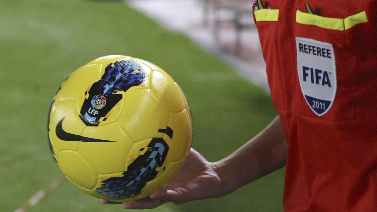 Un árbitro sujeta un balón de fútbol