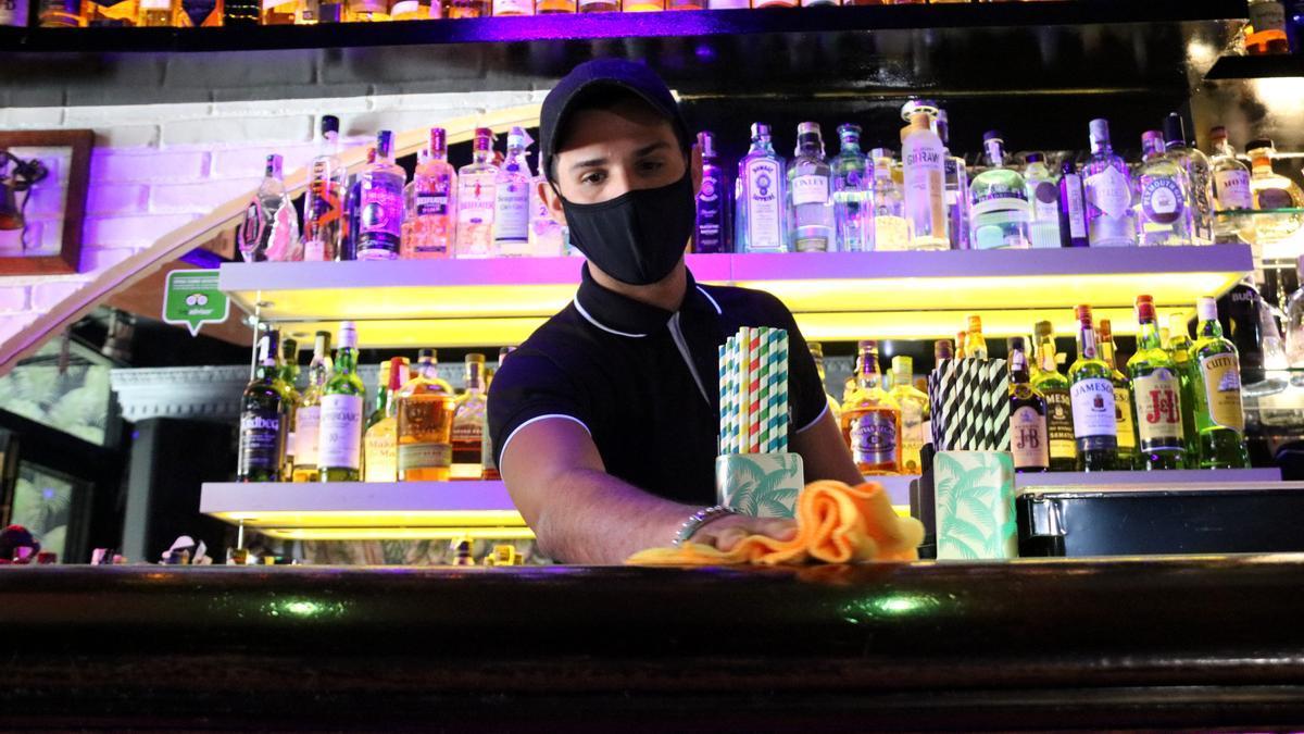 Pla curt d'un treballador d'un local d'oci nocturn de Sitges participant a l'assiag clínic en el moment que neteja la barra del bar. Imatge publicada el 10 de maig del 2021 (horitzontal)