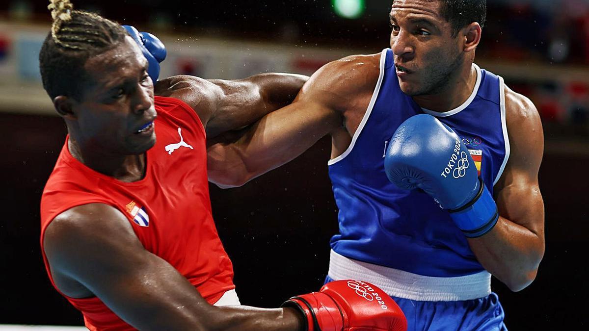 Enmanuel Reyes, de azul, golpea a Julio la Cruz, de rojo, en el combate de ayer.    // REUTERS