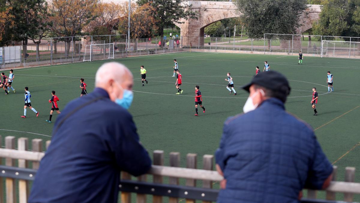 Dos hombres observan un partido de futbol base desde el Pont de Fusta.