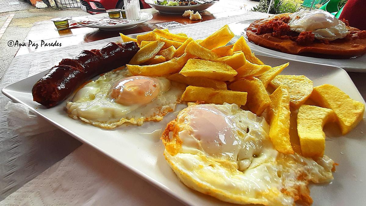 Patatas fritas, huevos y chorizo frito en primer plano. Detrás, torto con picadilllo y huevo. Dos especialidades del Chigre de Arenes, en Arenes de Parres