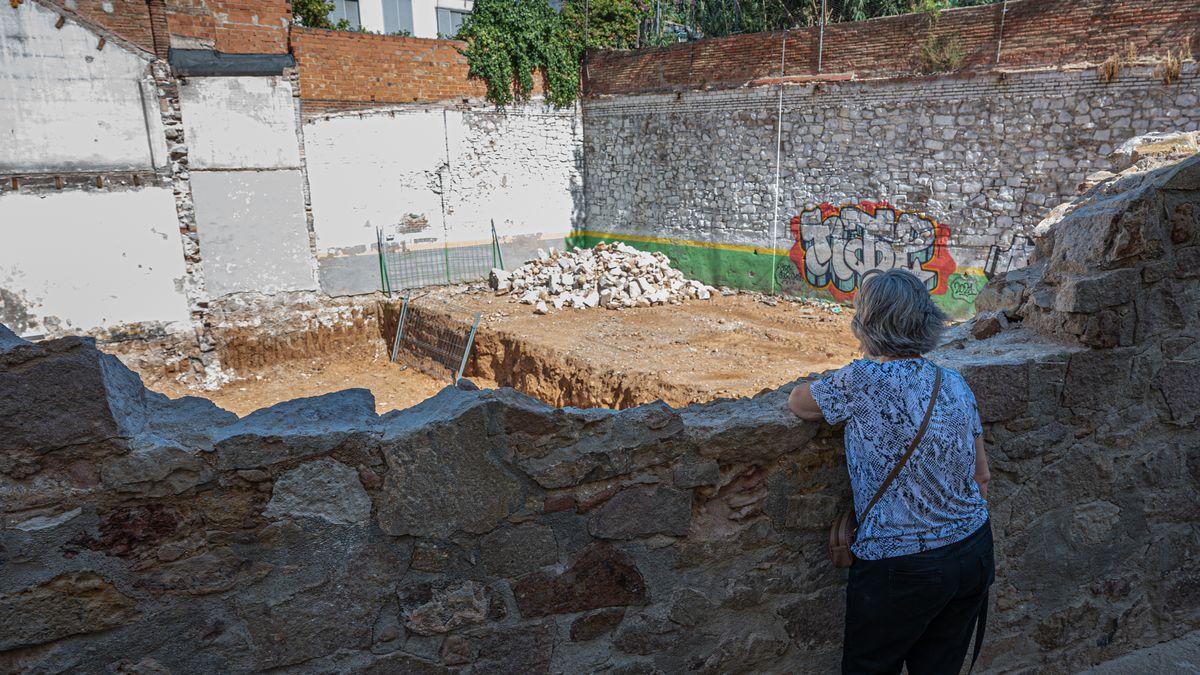 Una vecina contempla la obra del solar desde la parte de muro derribado.