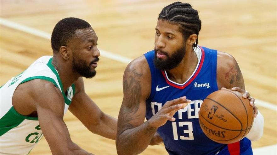 Paul George, de los Clippers, intenta penetrar a canasta mientras es defendido por Kemba Walker, de los Celtics.