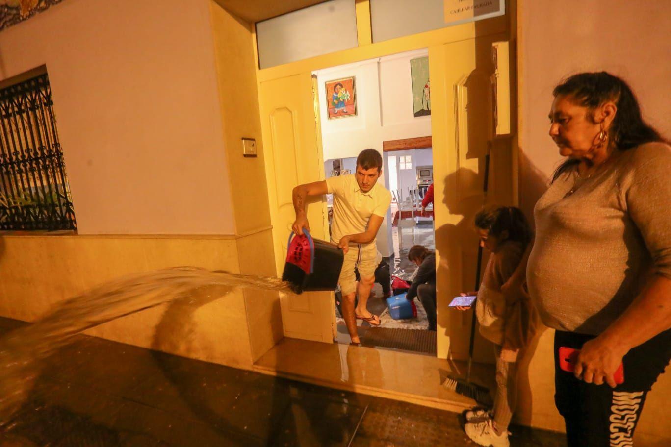 Vecinos del Cabanyal achican el agua que ha entrado en sus casas