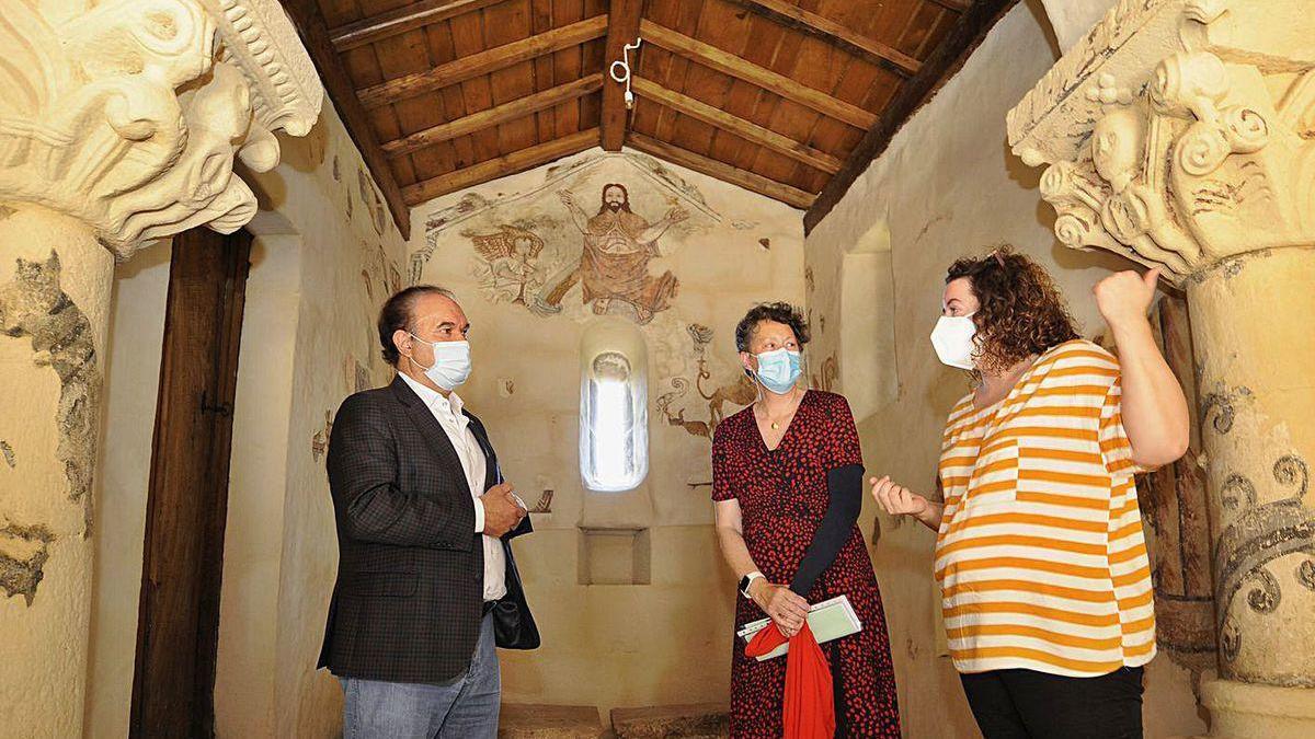 Arriba, José Crespo y Carmen Martínez atienden las explicaciones sobre la recuperación de las pinturas y otras partes del templo, como la tribuna, a la derecha.