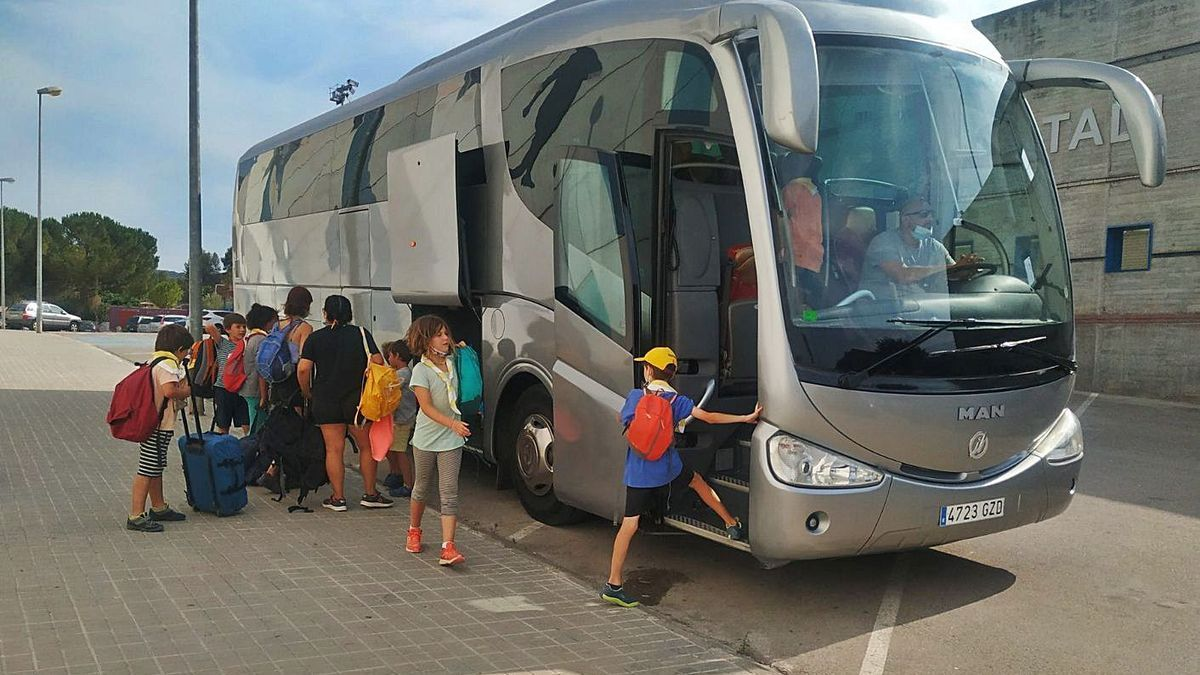Nens i monitors ahir a la tarda col·locant les motxilles al bus que els va anar a buscar | ABEL GALLARDO