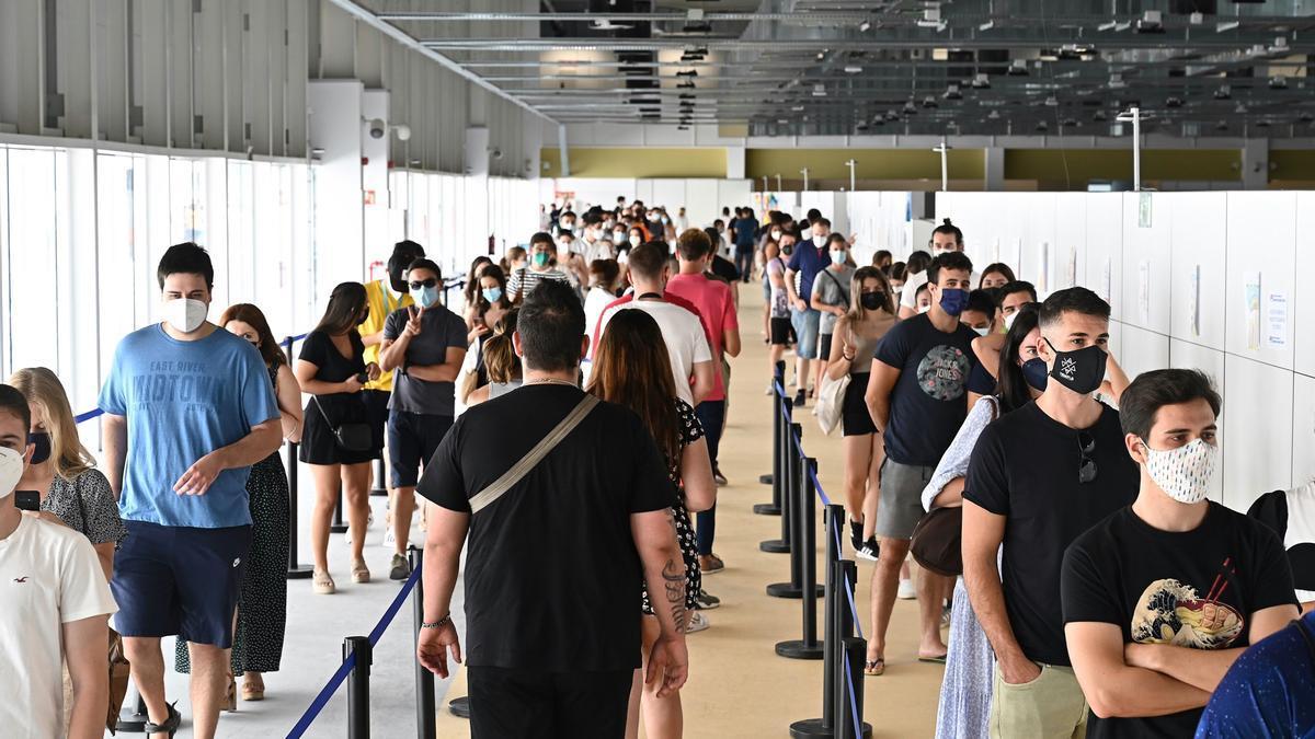 Jóvenes esperan para vacunarse en el Wizink Center de Madrid.
