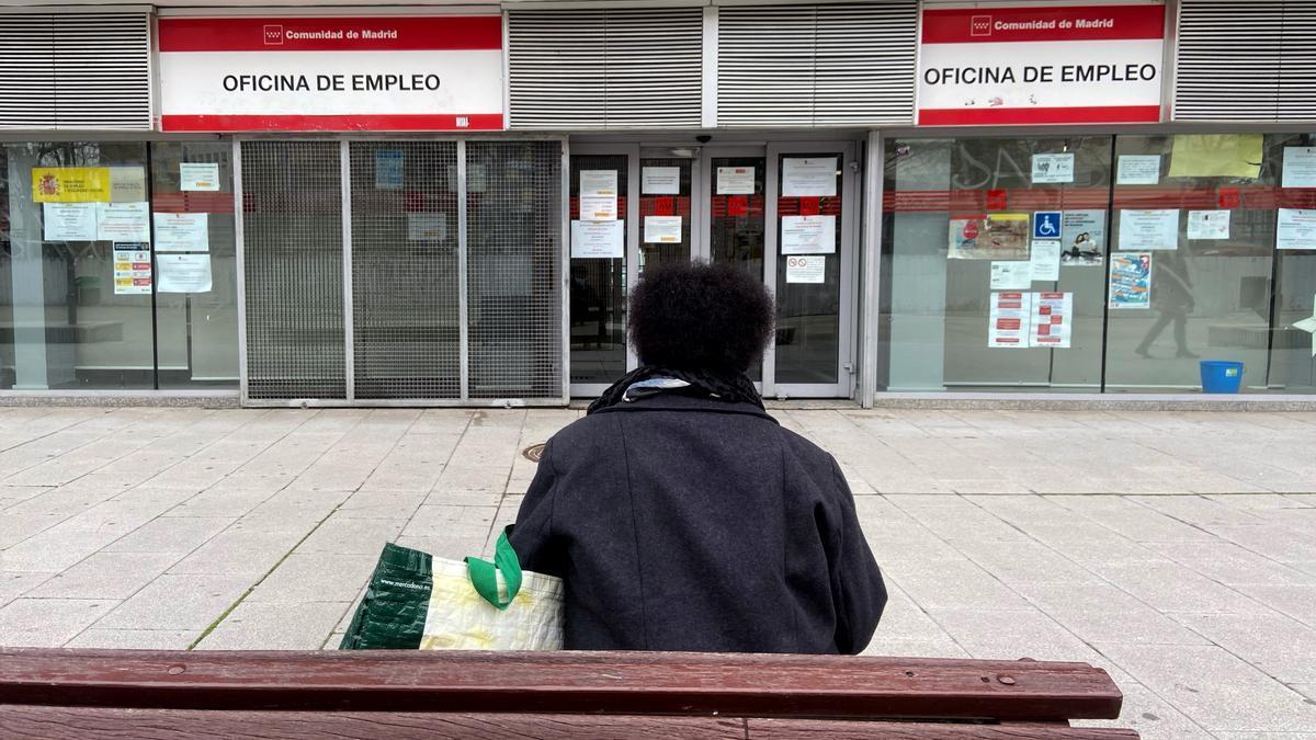 Una mujer frente a una oficina de empleo.