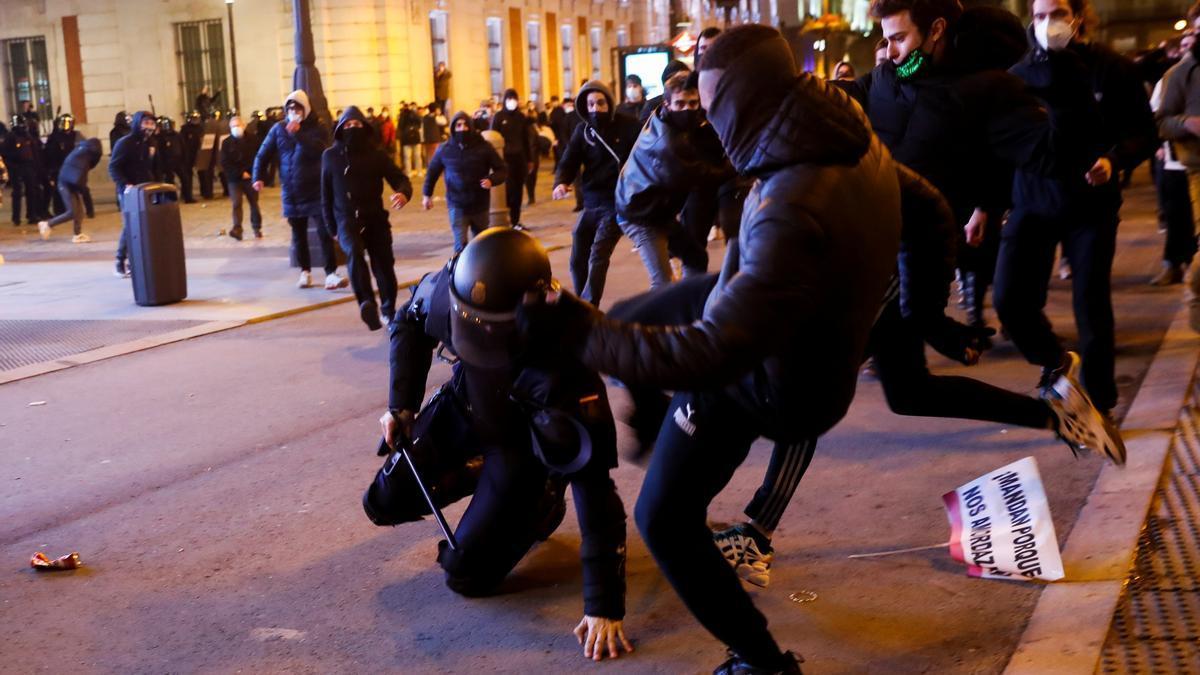 Dos manifestantes agreden a un policía en Madrid en las protestas por Pablo Hasél.