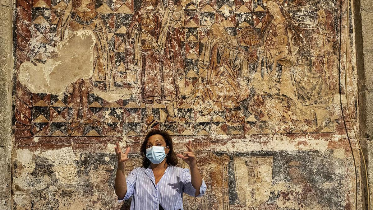 La restauradora, Vania López, explicando su intervención para recuperar los murales, con la adoración de los Reyes Magos a su espalda. |   // BRAIS LORENZO