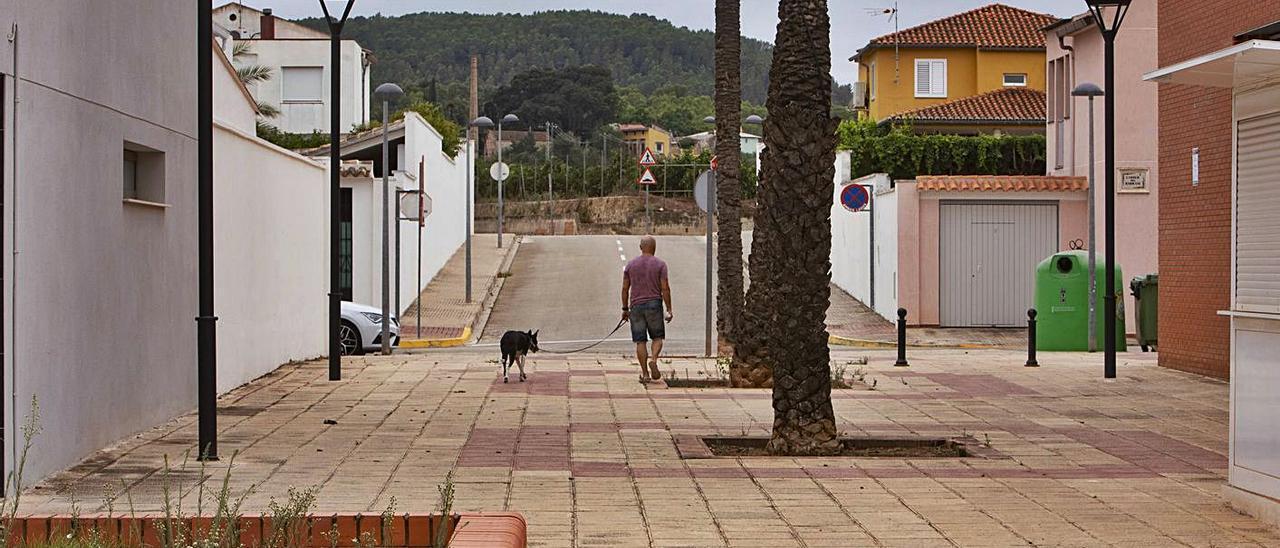 Un vecino de Beneixida pasea a su perro, en una imagen tomada ayer.   PERALES IBORRA