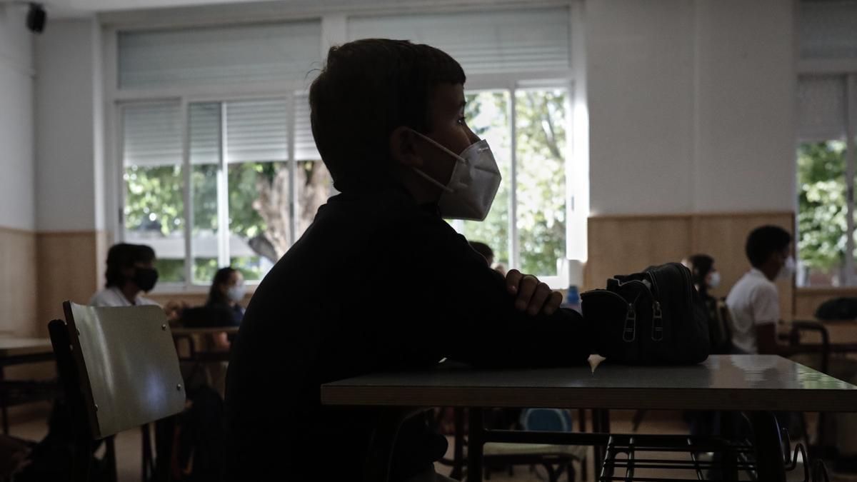 Un alumno con mascarilla en un aula.