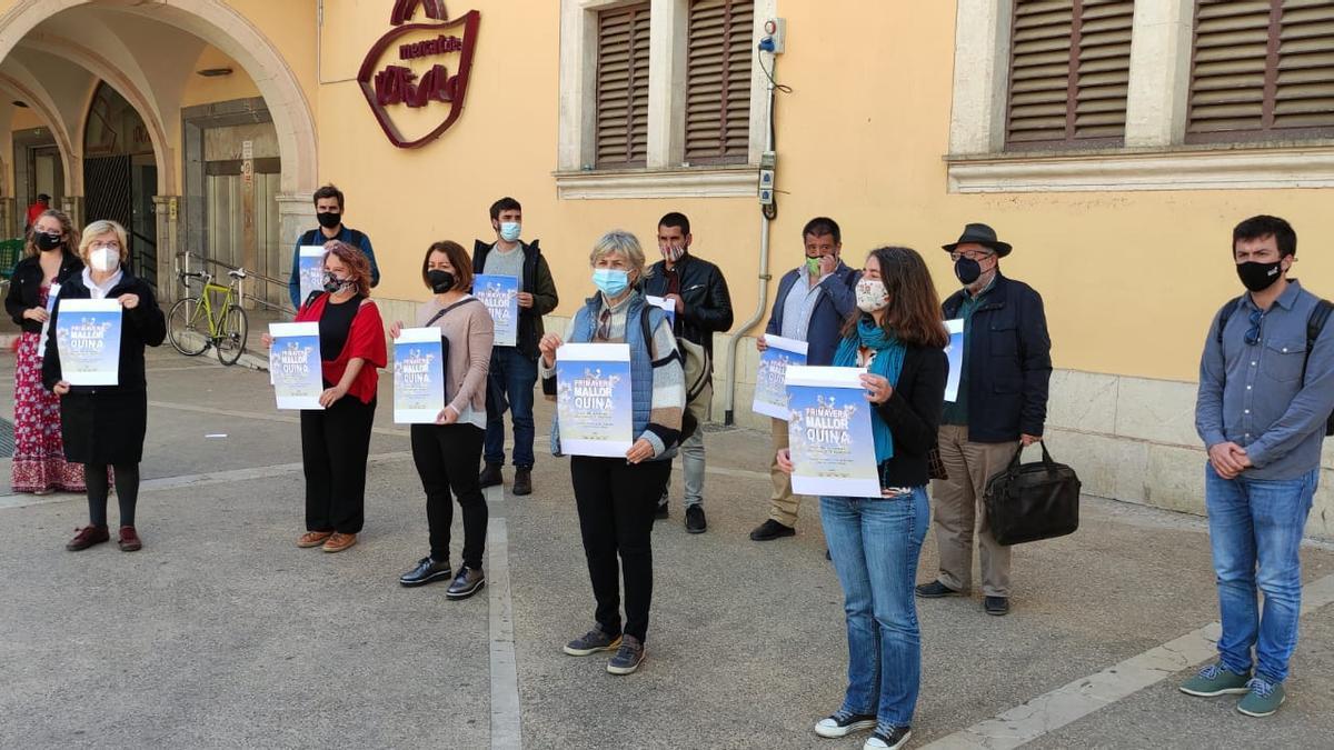 """Los organizadores del acto de homenaje posando con el cartel de """"Primavera Mallorquina""""."""
