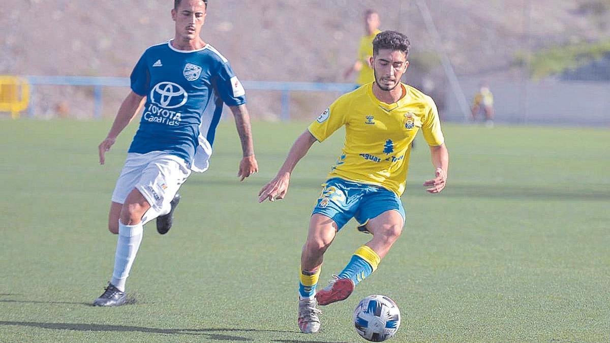 Idafe, jugador de Las Palmas C, perseguido por Omar Velázquez, futbolista de la UD San Fernando.
